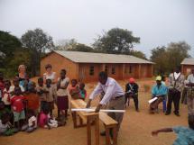presentatie schoolbankje aan alle mensen van Chimwemwe